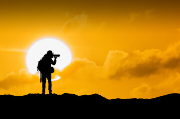 Wall Mural - Silhouette of photographer with camera at sunset.