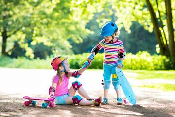 Children riding skateboard in summer park