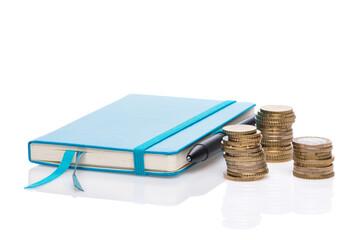 Münzstapel, Taschenrechner und Notizbuch