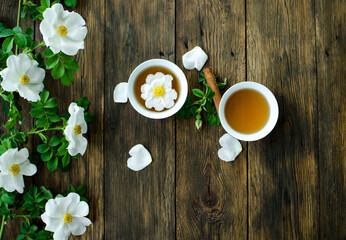 Cup of hot tea with rosehip and blooming flowers on old rustic wooden background