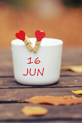 June 16th. Day 16 of month, color calendar on morning coffee cup at nature background. Summer concept. Empty space for text