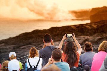 Tourists taking photos at Kalapana lava viewing area. Lava pouring into the ocean creating a huge poisonous plume of smoke at Hawaii's Kilauea Volcano, Big Island of Hawaii