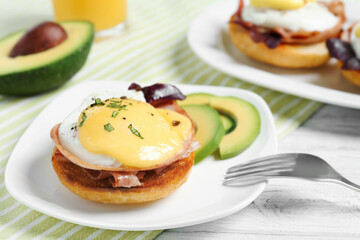 Tasty egg Benedict on wooden board
