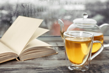 Cup of hot drink with teapot and open book on wooden windowsill