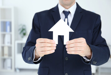 Man holding house model on blurred background