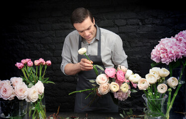 Handsome florist creating beautiful bouquet in flower shop