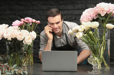 Handsome florist talking by mobile phone at workplace in flower shop