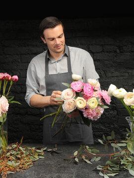 Handsome florist creating beautiful bouquet in flower shop