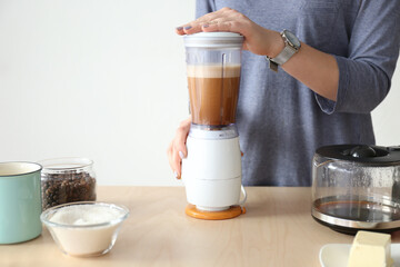 Woman using blender to make coffee with butter