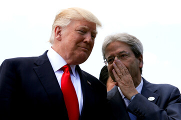 Italian Prime Minister Paolo Gentiloni speaks to U.S. President Donald Trump during a family photo at the G7 Summit expanded session in Taormina