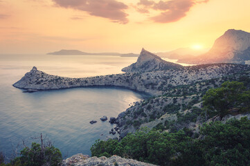 Wall Mural - Beautiful sunrise in mountains at the sea. Amazing summer landscape with rocks, mountain forest, colorful bright orange sky with sun, blue water in the morning. Seascape at dawn. Nature background