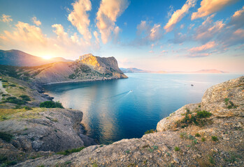 Wall Mural - Amazing mountain landscape at sunset. Beautiful scene with mountains, blue sea, high rocks, beach, forest and colorful blue sky with clouds in summer. Travel in Europe. Seascape. Nature background