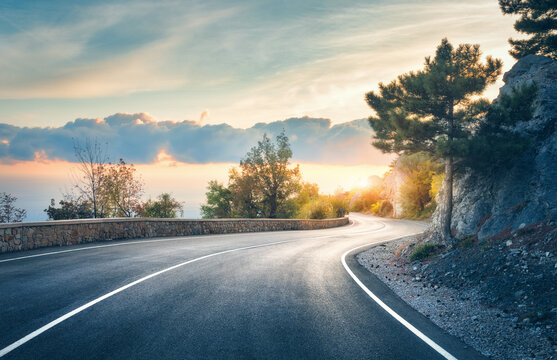 Mountain road. Landscape with rocks, sunny sky with clouds and beautiful asphalt road in the evening in summer. Vintage toning. Travel background. Highway in mountains. Transportation
