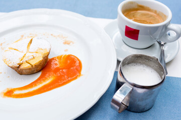 Viennese Apple strudel with fruit sauce on a plate. not a classic shape in a unique way. a Cup of coffee and a warm frothed milk