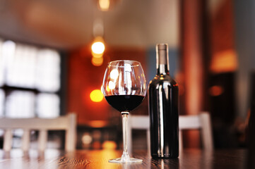 a glass of red dry wine with a bottle on a table