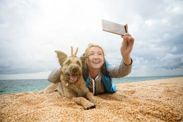 A young woman is photographed with a dog on the beach, they laugh and are amused.