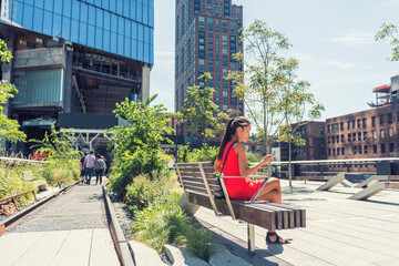 New York City lifestyle woman on mobile phone on urban high line park NYC. Tourist travel vacation girl sitting on beanch texting on smartphone app visiting Manhattan touristic attraction.