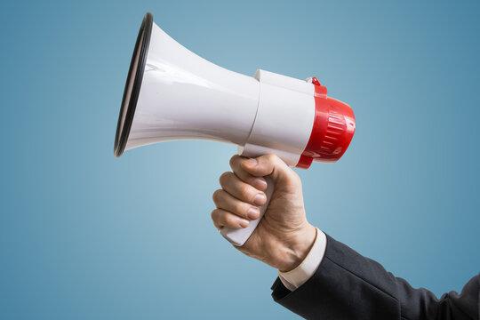 Announcement concept. Hand holds megaphone.