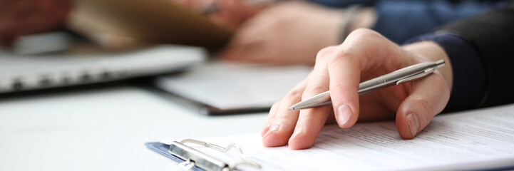 Hand of businessman signing document with pen