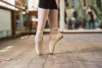 Feet of ballerina dancing in ballet shoes. Ballerina standing on toes