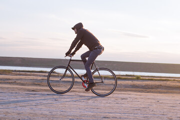 Alone rider on fixed gear road bike riding in the desert near river, hipster tourist bicycle rider pictures.