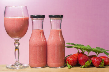 A glass and two bottles with strawberry smoothie on a pink background