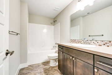 White bathroom interior with brown vanity cabinet