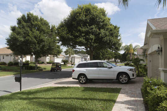 Luxury car parked on the driveway of a house in a Florida residential area reserved for mid aged people, USA 2017