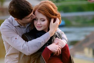 Redhead pretty girl in hugs of handsome brunette man, romantic moment