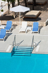 sunbeds and umbrellas by the swimming pool on a sunny day