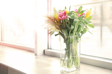 Vase with bouquet of beautiful tulips on windowsill