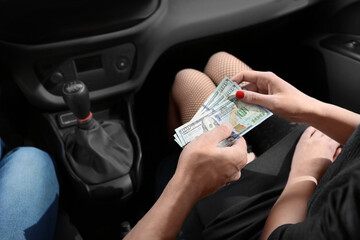 Young prostitute receiving money from client in car