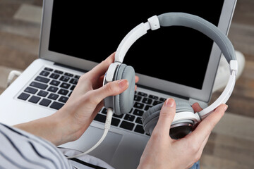 Woman with modern laptop and headphones sitting on floor. Concept of audiobook