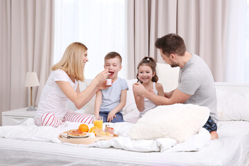 Happy smiling family having breakfast in bed