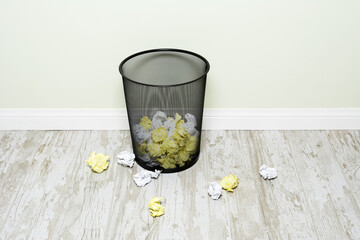 Crumpled paper in wastepaper basket