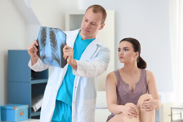 Male orthopedist with patient in clinic