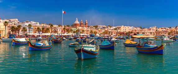 Panorama with raditional eyed colorful boats Luzzu in the Harbor of Mediterranean fishing village Marsaxlokk, Malta