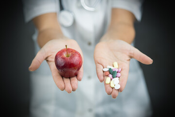 Woman young doctor standing and giving healthy fruit apple and pills