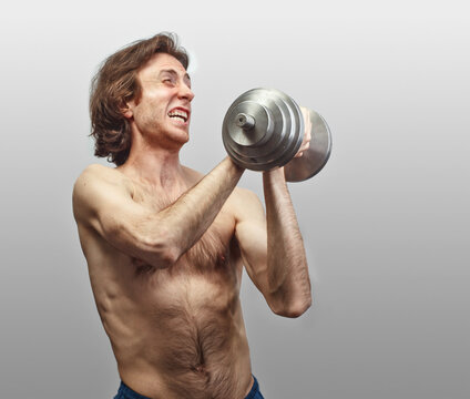 weak man trying lift up heavy dumbbell isolate on studio background