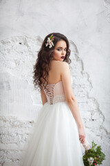 Portrait of a beautiful young girl of European appearance in a stylish white wedding dress with a hairdo and makeup with a wedding bouquet in the hands of fine flowers
