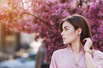 Outdoor close up portrait of  young beautiful fashionable girl posing on street, looking aside. Model wearing pink dress, has stylish earrings, hand watch. Female fashion. Copy, empty space for text
