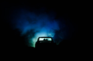 Poster Vintage voitures silhouette of car with couple inside on dark background with lights and smoke. Romantic scene. Love concept