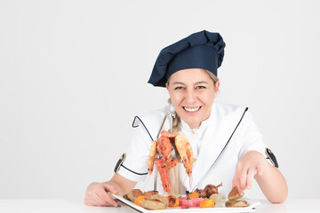 Chef with with blue white uniform posing in front of delicous shrimp sea food dish while sitting