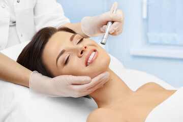 Cosmetology. Spa clinic. Beautiful woman at facial treatment procedure. Young healthy skin. Facial mask. Skin rejuvenation.