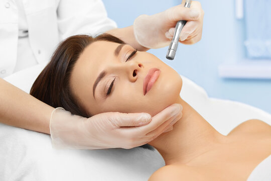 Cosmetology. Spa clinic. Beautiful woman at facial treatment procedure. Young healthy skin. Facial mask. Skin rejuvenation.