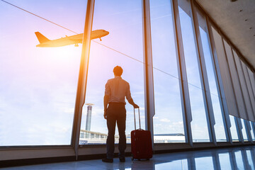 Businessman with suitcase at airport international departure gate, flying airplane