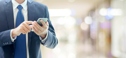 Business man hands using smart phone over blur office with copy space background, businessman on phone