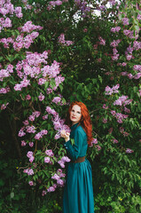 The red-haired girl is standing near the lilac bush