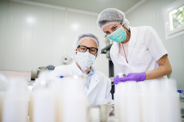Doctor and nurse doing chemical analysis in a cosmetic production laboratory.