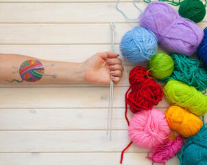 A woman with a tattoo in the form of a ball of wool keeps the skein. Background of white wood.